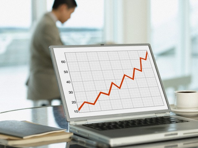 Graph showing profit on laptop with businessman working in the office